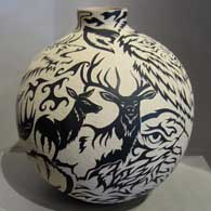 Sgraffito stylized animal design on a black and white jar