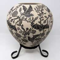 Sgraffito bat and branch design on a black and white jar with a custom stand