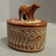Lidded red jar incised with feather and geometric design