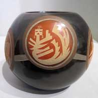 Sienna spots and sgraffito yei and geometric design on a black jar
