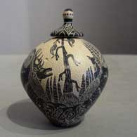 Sgraffito nature and wildlife design on a lidded black and white jar