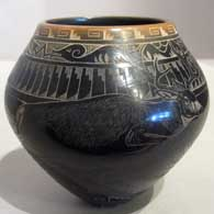 Sgraffito designs and a sienna rim on a black jar