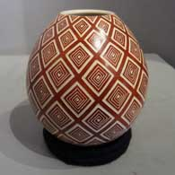 Sgraffito geometric design on a red and white jar