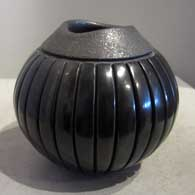 Carved black melon bowl with an organic opening and micaceous slip around the rim
