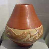 Avanyu design carved into a red and tan jar