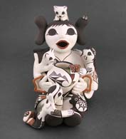 Two children on an Acoma grandmother storyteller figure with an assortment of gifts and household pets