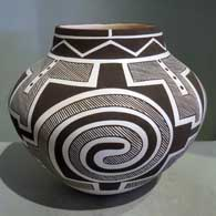 This black and white jar incorporating Tularosa and Mimbres designs was created by Myron Sarracino of Laguna Pueblo
