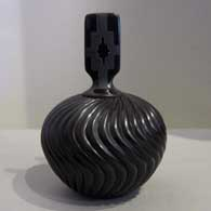 Melon design carved into a lidded black jar