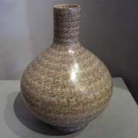Geometric design on a tall-neck polychrome jar with a matching stand