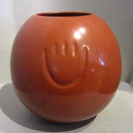 Bear paw imprint on a polished red pot by Tina Garcia