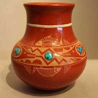 Three inlaid turquoise and sgraffito avanyu desighn on a polished red jar