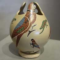 Sgraffito and painted multicolored parrt design on a sculptured jar