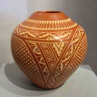Sgraffito geometric design on a red jar