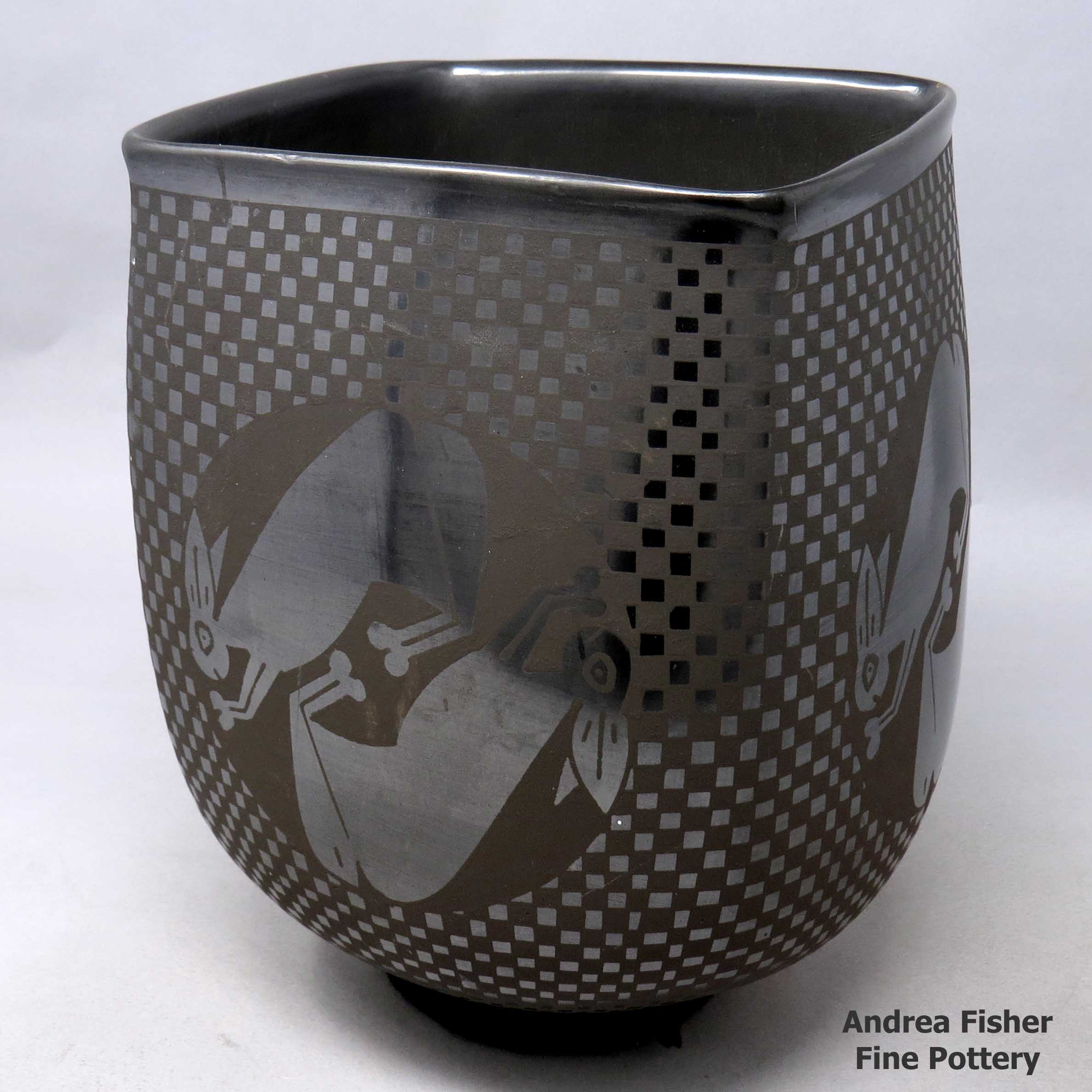 Squarish black on black jar with rabbit medallions and quadrillos design  made by Macario Ortiz of Mata Ortiz and Casas Grandes