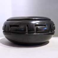 Black jar carved with a geometric design  , click or tap to see a larger version