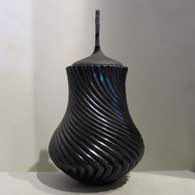 Lidded, polished black jar carved with swirl design Generations , click or tap to see a larger version