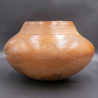 Brown jar with carved hand and geometric design, click or tap to see a larger version
