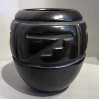 Black jar carved with four panel geometric design, click or tap to see a larger version