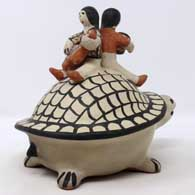 2 children sitting on the back of a turtle figure , click or tap to see a larger version