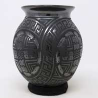 Black on black jar with formed bulges and geometric design , click or tap to see a larger version