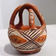 Polychrome friendship basket with twisted handle and geometric design  , click or tap to see a larger version