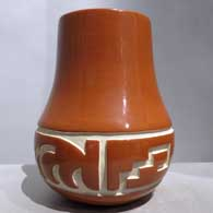 Red jar carved with a stylized avanyu and geometric design, click or tap to see a larger version