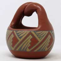 Polychrome basket with twisted handle and geometric design , click or tap to see a larger version