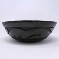 Black bowl carved with an avanyu design , click or tap to see a larger version